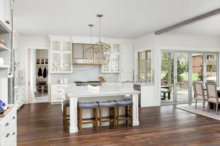 Large open concept white kitchen that has a huge square island
