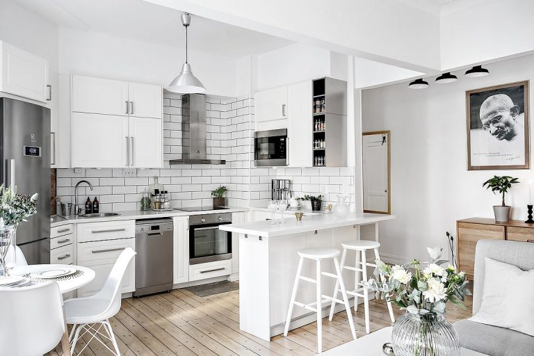 U-Shaped Kitchen with Wood Flooring and White Brick Backsplash